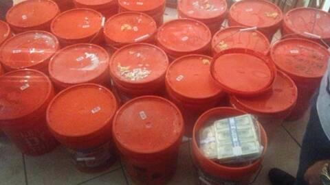 La policía encontró el dinero dentro de cubos de 5 galones...