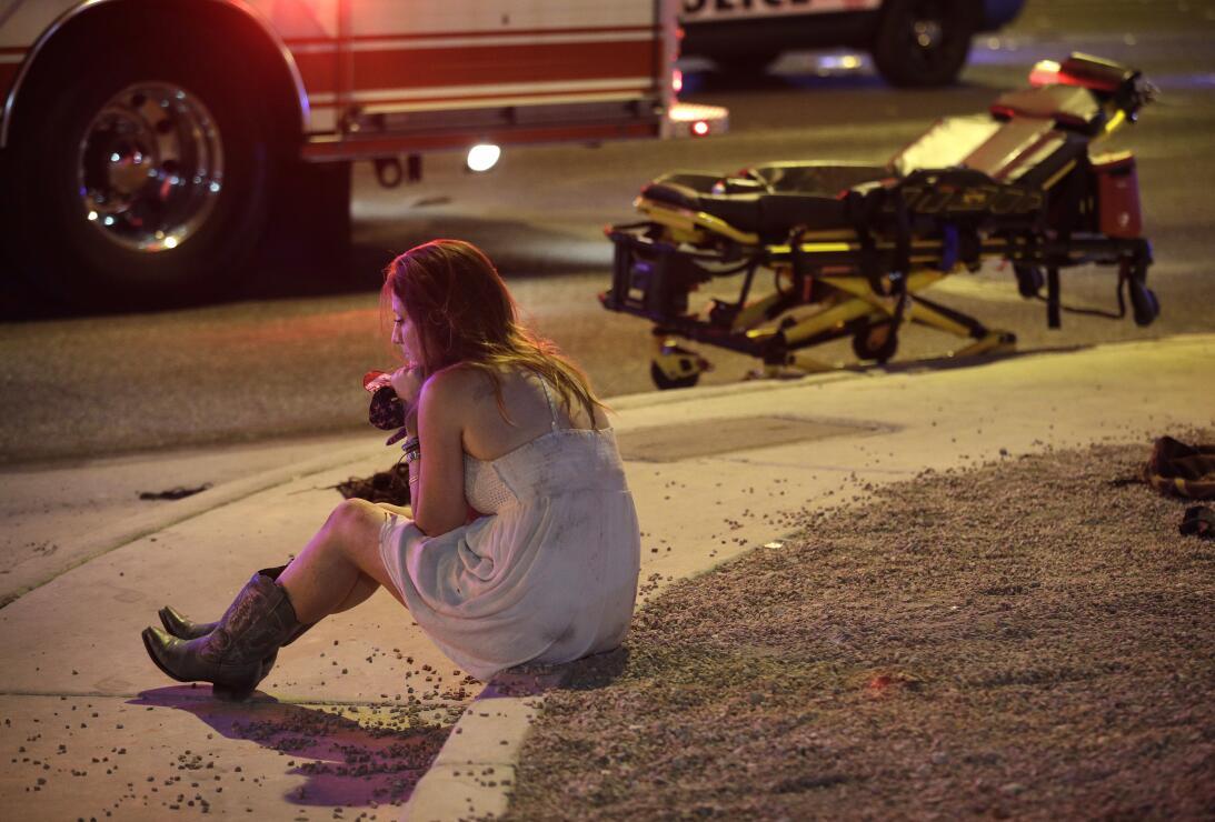 Una mujer, junto a una camilla, espera asistencia sentada en una vereda...