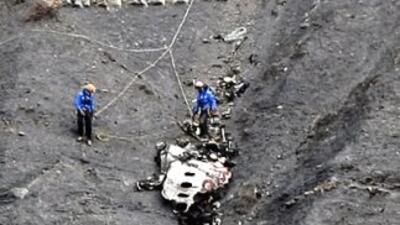 Dos rescatistas junto a una de las partes del fuselaje del Airbus A320 d...