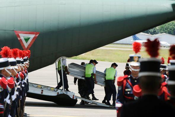 Tras ser desembarcados del avión, los ataúdes grises con los hondureños...