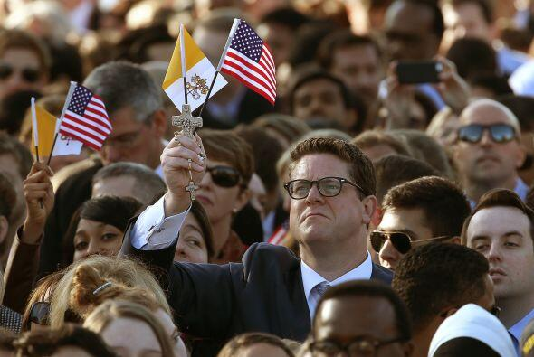Entre la multitud, este hombre sostiene en su mano derecha una bandera d...