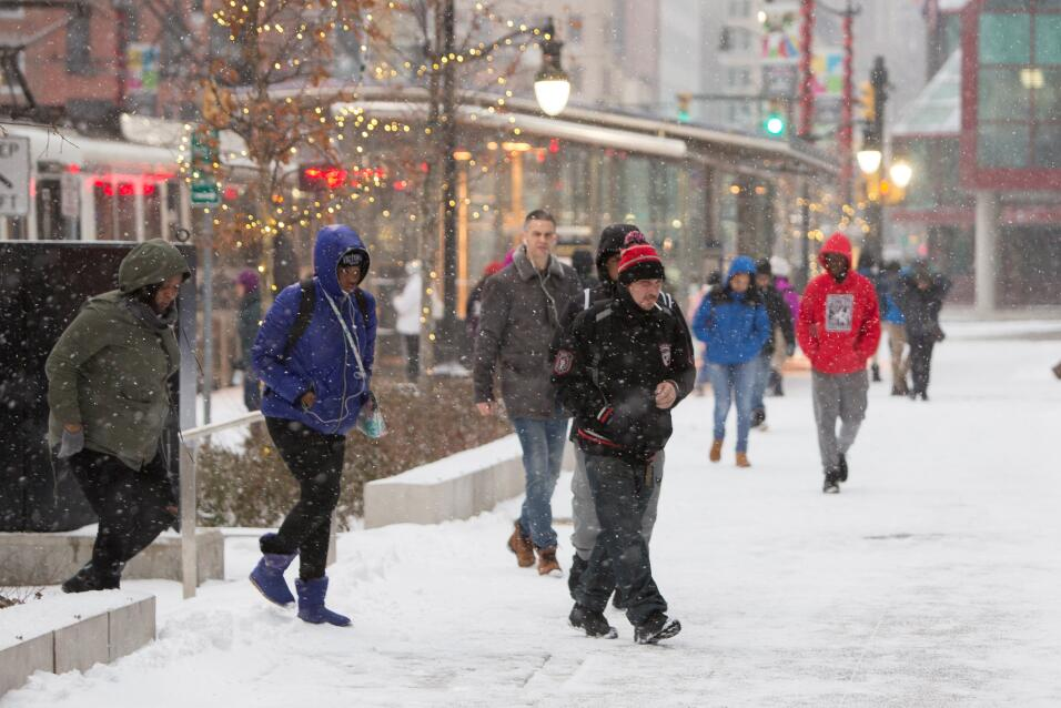 People walking during the first lake effect snowfall of the season in do...