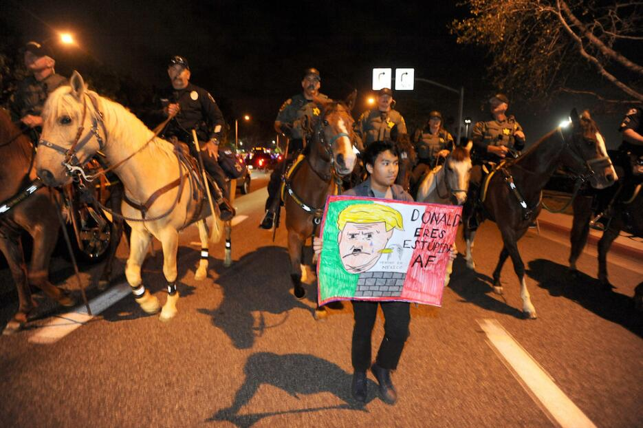 Police on horseback and on foot clear the anti-Trump demonstrators after...