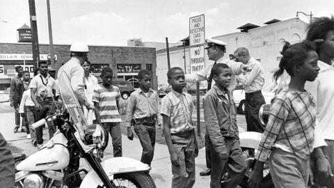 Policías conducen a un grupo de niños negros a la c&aacute...