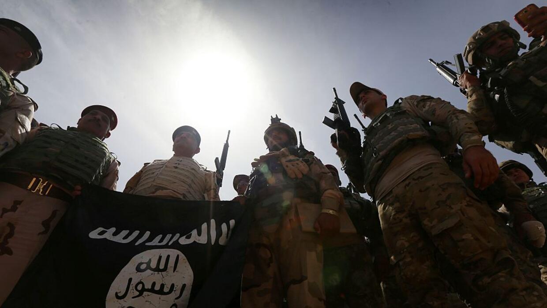 Soldados iraquíes sostienen una bandera de ISIS tras tomar el control de...