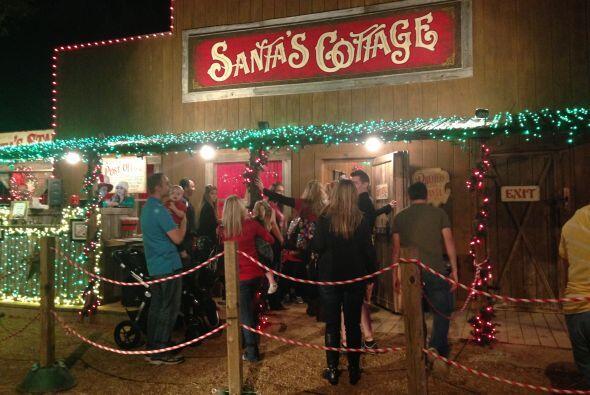 Otros esperan en línea para tomarse la foto con Santa Claus en Santa's C...