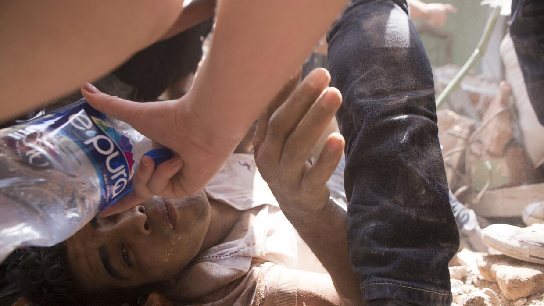 Equipos de emergencia dan agua a un hombre que está siendo rescatado en...
