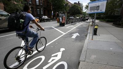 Un ciclista va por una ciclovía entre autos estacionados y la acera en B...