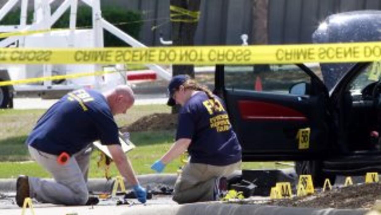Policías buscan pistas en el estacionamiento donde fueron abatidos los d...
