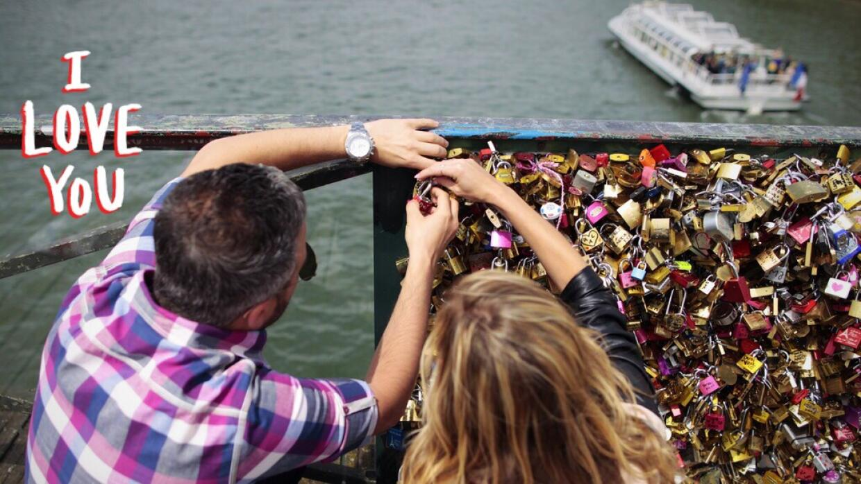 A couple locks a padlock on the 'Pont des Arts'