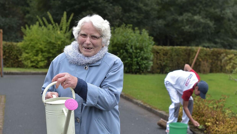 Una mujer con Alzheimer riega el jardín junto a un joven con dificultade...