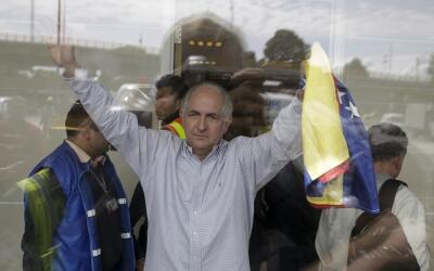 Antonio Ledezma sostiene una bandera nacional venezolana en el aeropuert...