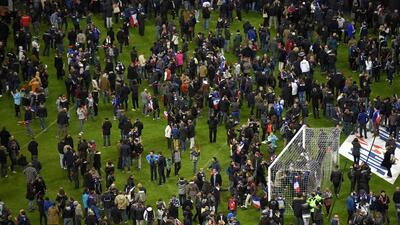 Aficionados en la grama del Stade de France luego de las explosiones.