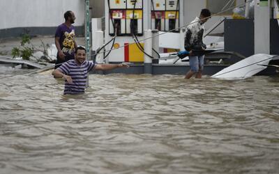 Residentes de Humacao, Puerto Rico, caminan junto a una gasolinera inund...