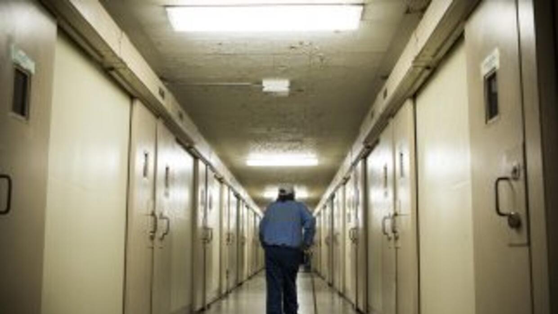 La imagen muestra a un preso caminando por un pasillo de una prisión en...