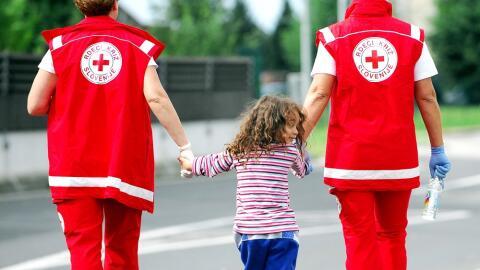 Trabajadores de la Cruz Roja con una niña siria en la frontera de...