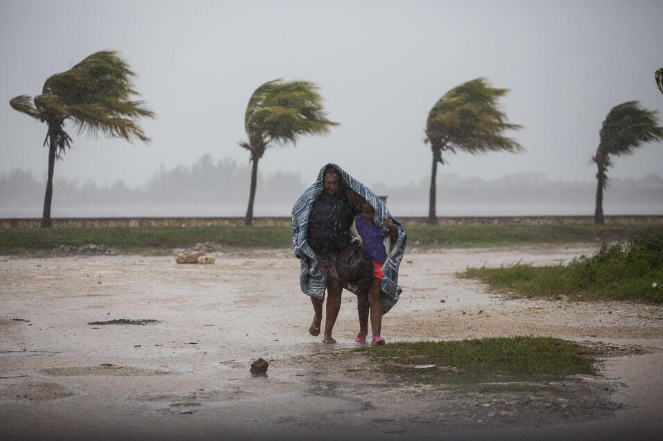 Una mujer y un niño bajo una manta se protegen contra el viento y...