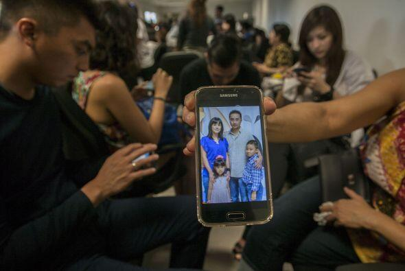 Esta persona muestra una fotografía con los miembros de su familia que v...
