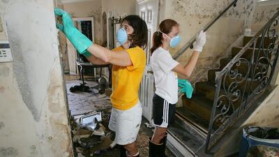 Una madre y su hija sacan la pintura y el moho en una vivienda después d...