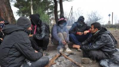 Un grupo de inmigrantes intenta calentarse en un día frío en Macedonia.